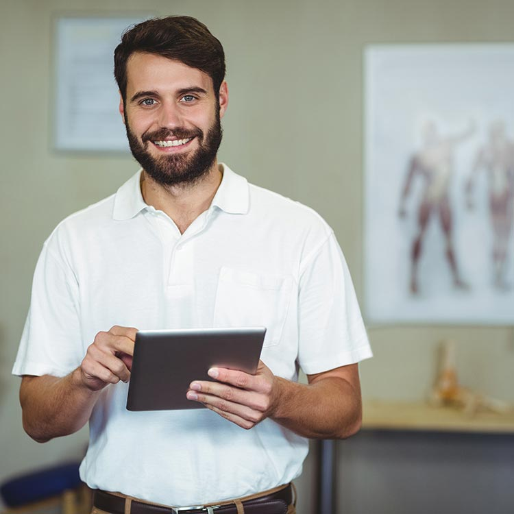 Physical therapist smiling and using CONNECT Rehab EMR software