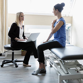 Physical therapist using CONNECT rehab EMR software while talking to patient